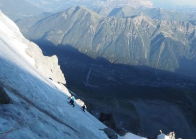 Traverse leftwards around the top rock buttress